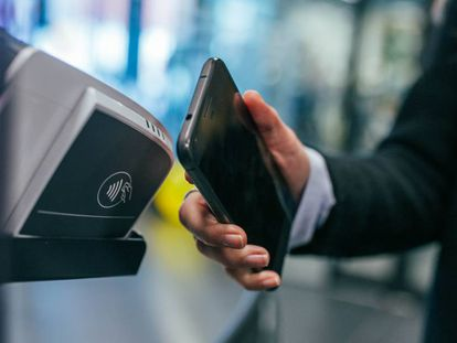 Un usuario paga una compra con tecnología NFC a través de su móvil.