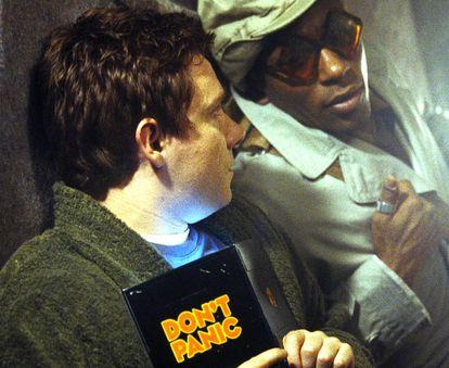 Imagen de la película que adaptó la 'Guía del autoestopista galáctico' de Douglas Adams, con Arthur Dent, su protagonista, sujetando la guía en cuestión.