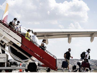 Viajeros descienden de la escalerilla de un avión de Iberia.