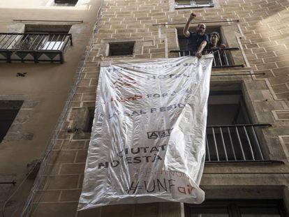 Unos vecinos desplegando una pancarta contra los pisos turísticos.
