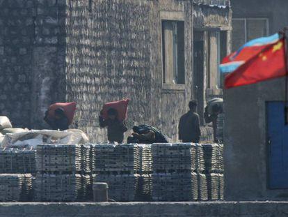 Norcoreanos cargan sacos en un astillero de Sinuiju. Del otro lado, la localidad china de Dandong.