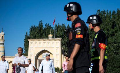 Unos policías chinos vigilan la salida de unos uigures de una mezquita, en 2017 en Kashgar.