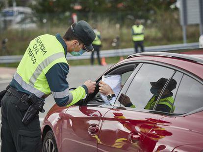 Un agente de la Guardia Civil de Tráfico comprueba la documentación de un conductor en un control policial en el límite provincial entre Navarra y Álava en 2020.