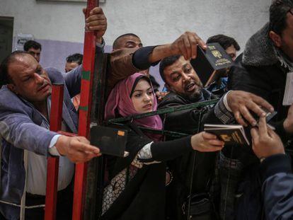 Un grupo de palestinos espera a cruzar a Egipto en el paso de Rafah, en la franja de Gaza.