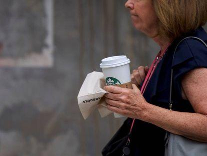 Una clienta con un café de la cadena Starbucks