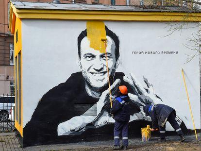 Un trabajador pinta sobre un grafiti con el retrato del opositor ruso Alexéi Navalni.