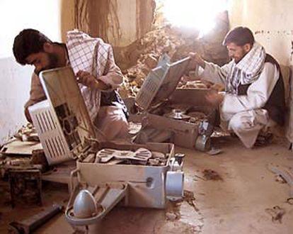 Kajam (izquierda) y el farmacéutico Assadallah observan los restos de dos proyectores de cine.