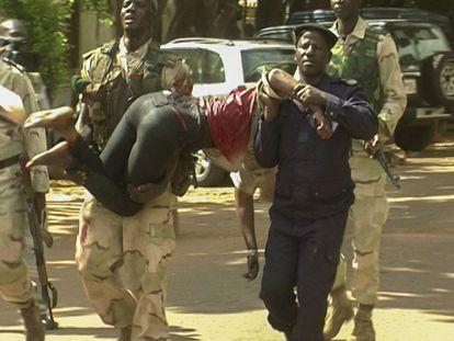 Personal militar de Mali traslada a una mujer herida a su salida del hotel.