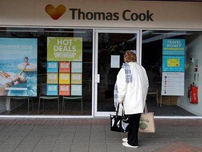 Una mujer delante de una oficina de Thomas Cook en el Reino Unido.