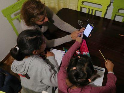 Flor Pérez Carrillo ayuda a hacer los deberes a sus dos hijas de 9 y 6 años, en su casa de Madrid, con la única ayuda de un móvil, ya que no han llegado las tabletas y portátiles prometidos por el ministerio y las comunidades.