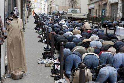Fieles musulmanes rezan en una calle de París junto a una mezquita.