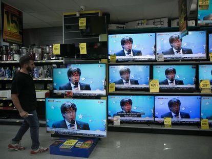 Rueda de prensa de Carles Puigdemont tras huir a Bruselas, en los televisores de una tienda de electrodomésticos de Barcelona.