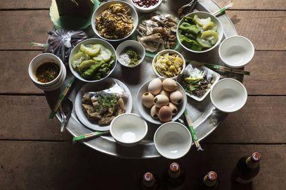 Comida con invitados en casa de Yayer y Ater: pollo relleno, verduras al vapor, salsa de chile, ensalada picante con carne, pollo cocido, huevos batidos a la parrilla… y cerveza BeerLao que solo beberán los hombres.
