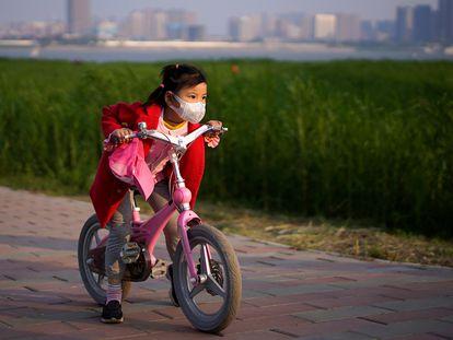 Una niña monta en bicicleta en un parque de Wuhan (China).