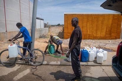 Varios jóvenes llenan garrafas de agua en una toma existente en el acerado de una de las calles del Polígono Industrial San Jorge, en la localidad onubense de Palos dela Frontera.