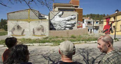 Integrantes del colectivo MIAU contemplan algunas obras pintadas en las fachadas de Fanzara.