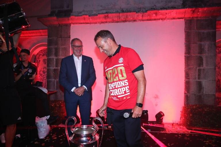 Hans Dieter Flick mira el trofeo de la Champions con Karl Heinz Rummenigge al fondo.