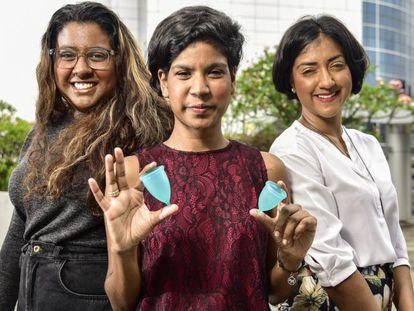 Las tres hermanas posan con la copa menstrual.