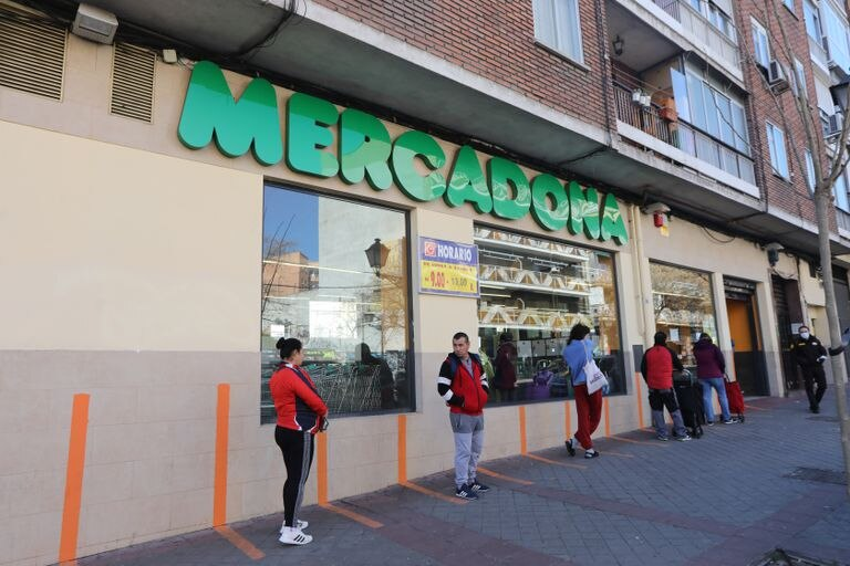 Clientes hacen cola a la entrada de un supermercado respectando la distancia de seguridad.