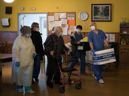 Personal de la residencia acompaña a una anciano tras la campaña de vacunas en el centro.