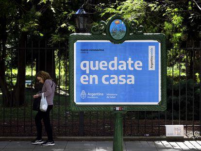 Una mujer pasa delante de un cartel el Gobierno que pide no salir a la calle como prevención ante el coronavirus.