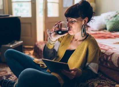 Una chica bebe una copa de vino mientras usa la tableta. GETTY