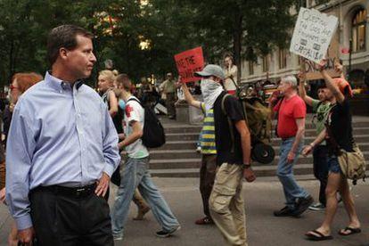 Un hombre de negocios observa a alguno de los manifestantes que forman parte del movimiento Occupy Wall Street.