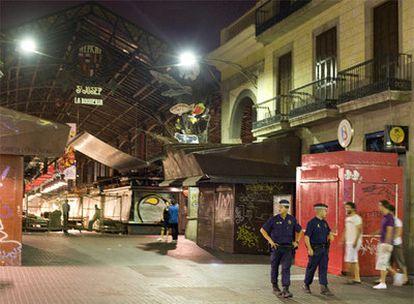 Agentes de la Guardia Urbana patrullan en la puerta del mercado de la Boqueria, durante la noche de ayer.