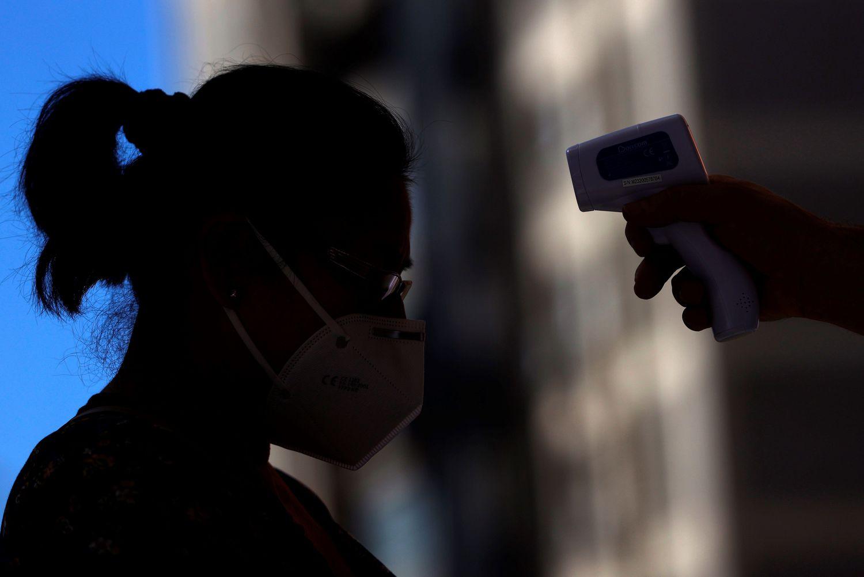 Un sanitario toma la temperatura a una mujer antes de acceder a un centro de salud.