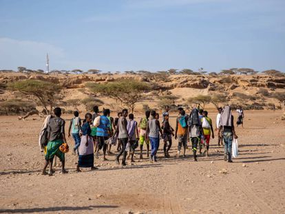 Migrantes etíopes en Obock, Djibouti, caminan hacia un área sombreada para esperar a que pasen contrabandistas y los lleven a Yemen en 2018.
