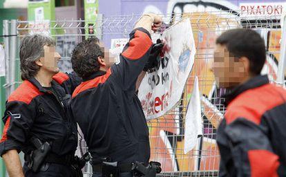 Miembros de la Ertzaintza procede a la retirada de carteles en las calles de Bilbao