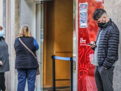 Un hombre joven mira su móvil mientras espera a la puerta de una oficina de empleo en Valencia.