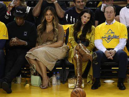 El rapero Jay-Z y la reina del pop Beyoncé junto a Nicole Curran y Joe Lacob (sí, él también estaba ahí) durante el polémico partido de baloncesto.