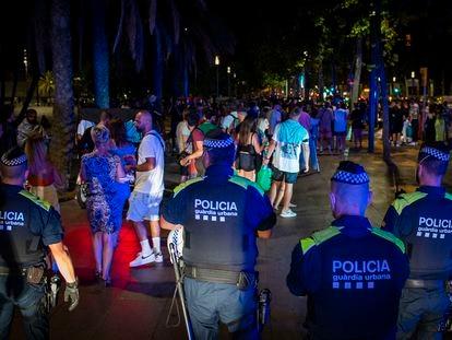 Guardias urbanos controlan un botellón en Barcelona.
