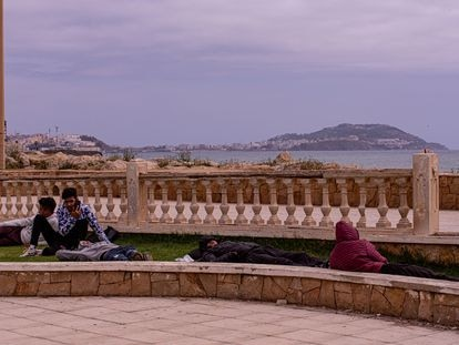 Varios jóvenes descansan en un jardín próximo al paseo marítimo de la ciudad de Castillejos (Fnideq en árabe), en Marruecos. Al fondo se observa la ciudad de Ceuta, el viernes.