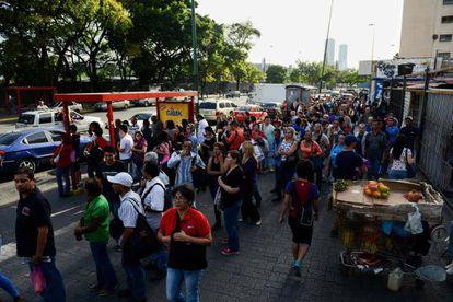 Un grupo de personas espera el autobús en Caracas.