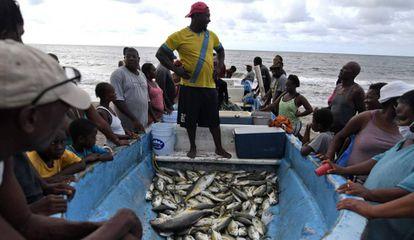 Miembros del grupo étnico garifuna rodean al pescador Santos Centeno para adquirir algo de pescado en la playa de Triunfo de la Cruz, en Honduras, el 5 de agosto de 2020.