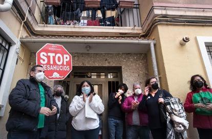 Lucila Infante (de blanco) de 39 años y peruana de origen, frente al portal de su casa, acompañada de activistas de la Plataforma antidesahucios de Valencia, que evitaron el pasado mes que se quedaran en la calle.