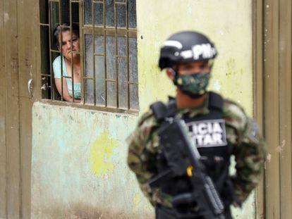 Una mujer observa desde su casa a un efectivo de la policía militar colombiana en el municipio de Soacha.