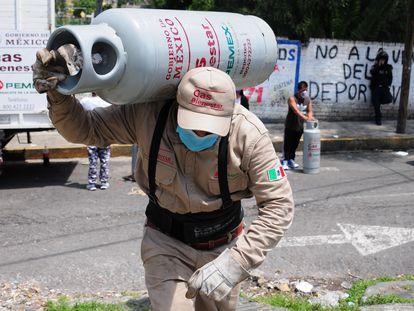 Un trabajador de Gas Bienestar carga un cilindro durante las pruebas piloto en la alcaldía Iztapalapa, en Ciudad de México.