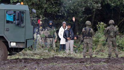 Agentes de fronteras de Polonia vigilan a un grupo de migrantes en la frontera con Polonia cerca de la localidad de Usnarz Gorny, el pasado 1 de septiembre.