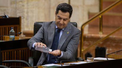 El presidente de la Junta de Andalucía, Juan Manuel Moreno, se desinfecta las manos durante la sesión de control al Gobierno, este miércoles.