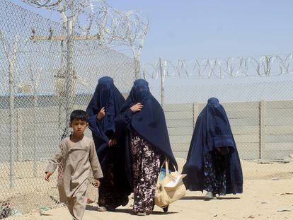 Mujeres y niños afganos, junto a la valla que separa la frontera entre Pakistán y Afganistán en la localidad paquistaní de Chaman, este sábado.