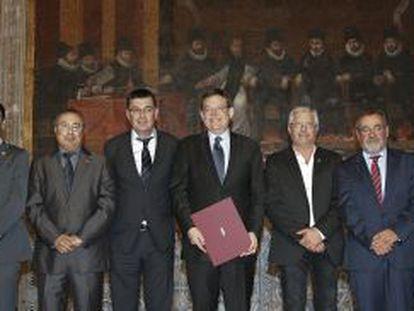 El presidente la Generalitat, en el centro con el acuerdo, posa con los rectores, los representantes de los agentes sociales y el presidente de las Cortes.