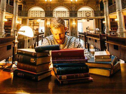 Un hombre estudia en una biblioteca.