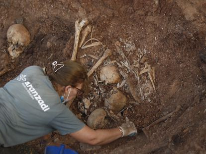 Concha González limpia unos restos bajo una de las carpas de la fosa de Pico Reja, en el cementerio de San Fernando, en Sevilla.