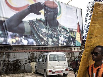 Un vendedor de gafas de sol pasa delante de un gran cartel donde aparece el teniente coronel Mamady Doumbouya, este 11 de septiembre en Conakry.