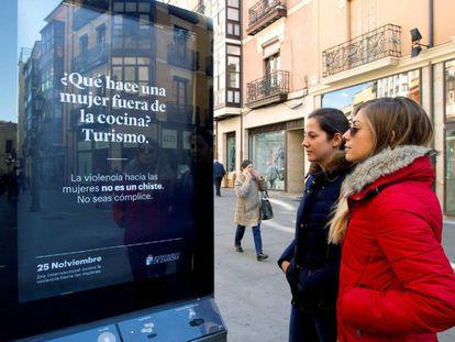 Dos mujeres observan un cartel en Zamora que busca concienciar sobre la violencia machista.