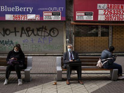 Un grupo de personas sentado fuera de las tiendas cerradas, el pasado 2 de septiembre de 2021 en Santiago de Chile.