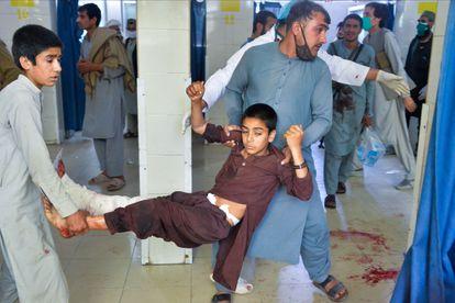Dos voluntarios llevan a un menor herido tras el ataque en un funeral en Nangarhar, en el este de Afganistán.